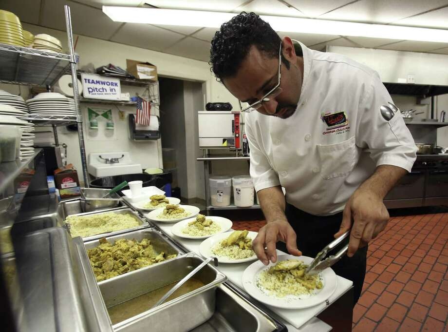 Chef Neil Hajji plates the chicken tagine and couscous he prepared as part of the San Antonio AIDS Foundation's Chef of the Month program. Photo: Photos By Helen L. Montoya / San Antonio Express-News