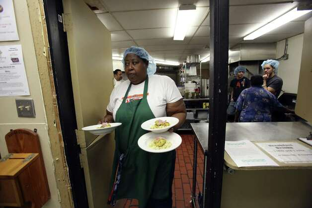 Theresa Haywood-Castile delivers entrées to participants in the foundation's Hot Meals Program, which offers free meals 365 days a year to those infected with HIV.