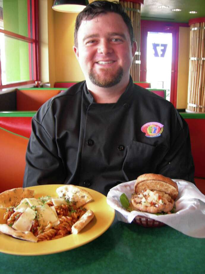 EZ's corporate chef Aaron Kolitz displays two of his new menu items, Bison Bolognese Pasta and Baja Salmon Burger. Photo: Stefanie Arias / San Antonio Express-News