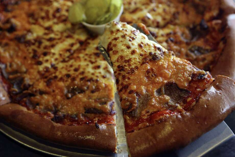 The Heaven's Brisket pizza has house-made brisket on top of a thick crust. It's different but worth trying. Photo: Photos By Helen L. Montoya / San Antonio Express-News