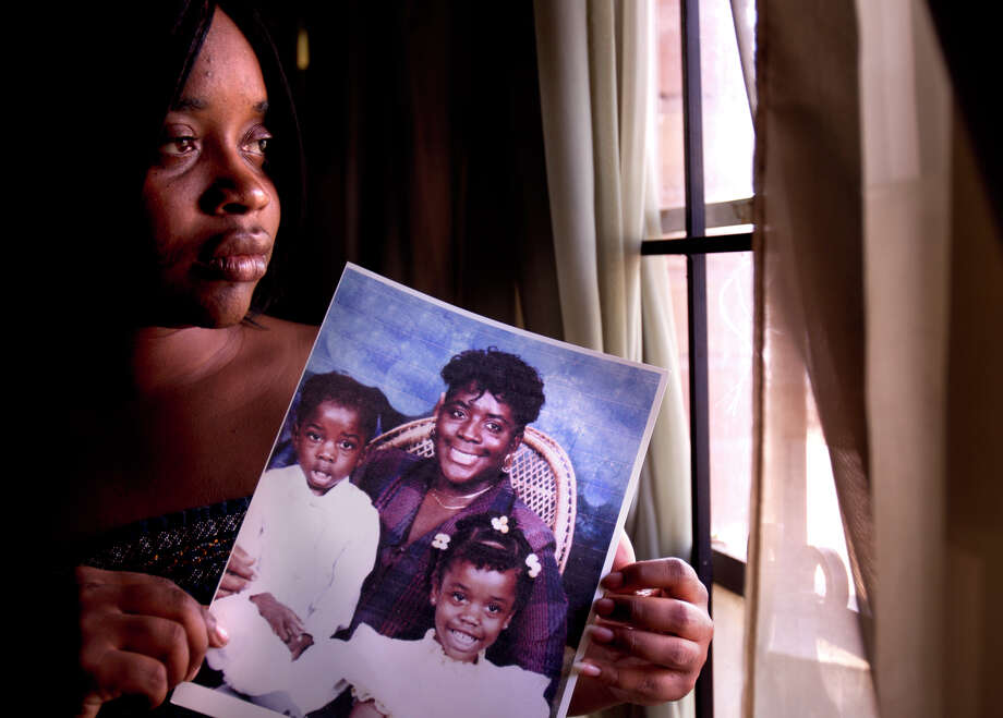 Shennel Gardner holds a portrait of her brother Devon Green, left; her mother, Debra Gardner, center; and herself, right; at a Gardner family home in Houston. Both Shennel and Devon were present when their mother, Debra, was shot by Duane Edward Buck in 1995. Photo: Cody Duty, Staff / © 2011 Houston Chronicle