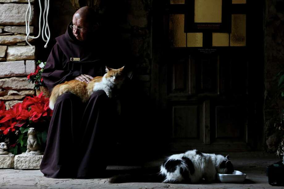 Brother Jerome Wolnick pets Moses as Dominic eats breakfast at Mission Espada, on Wednesday, Feb. 20, 2013. Photo: Lisa Krantz, San Antonio Express-News / San Antonio Express-News