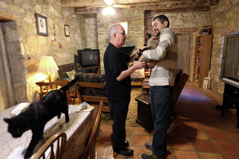 Mission San Juan Capistrano Father Jim Gavin gets Cappucino from  Robinson Maturana while Chico, left, roams the room, Tuesday, March 5, 2013. Rev. Gavin has kept cats at the mission and they  are known to keep the grounds free of rodents and snakes. Photo: Jerry Lara, San Antonio Express-News / © 2013 San Antonio Express-News