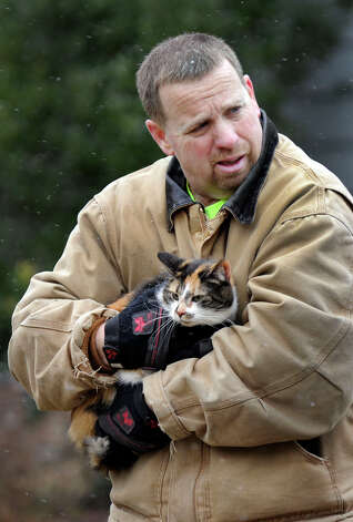 Chris McCollum with the Bethel Fire Dept. Holds a cat that was removed from a house fire on Reservoir Street in Bethel, Thursday, March 7, 2013. Photo: Carol Kaliff / The News-Times