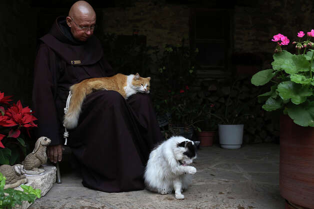 Brother Jerome Wolnick pets Moses as Dominic cleans himself after eating breakfast at Mission Espada, on Wednesday, Feb. 20, 2013. Photo: Lisa Krantz, San Antonio Express-News / San Antonio Express-News