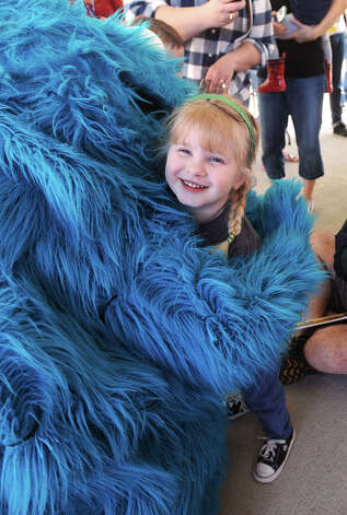 Ellie Shipp-George, 4, receives a hug from the Cookie Monster at the Beaumont Fire Museum on Thursday. Dozens of children attended the event to see Cookie Monster and Elmo.  Photo taken  Guiseppe Barranco/The Enterprise Photo: Guiseppe Barranco, STAFF PHOTOGRAPHER / The Beaumont Enterprise