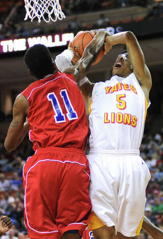 Yates' JC Washington (5) has his shot blocked by Royal's Kenton Sams (11) during the UIL 3A semi final boys basketball game between Houston Yates and Royal high schools on Thurs., March 7, 2013 at the Frank Erwin Center in Austin, TX.