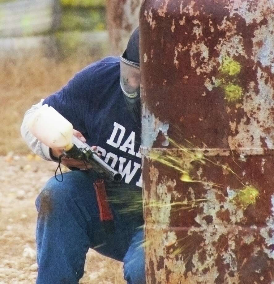 Phillip Call ducks back behind a barrier as a paintball targeted at him explodes. Photo by Joshua Trudell//Special to the Express-News