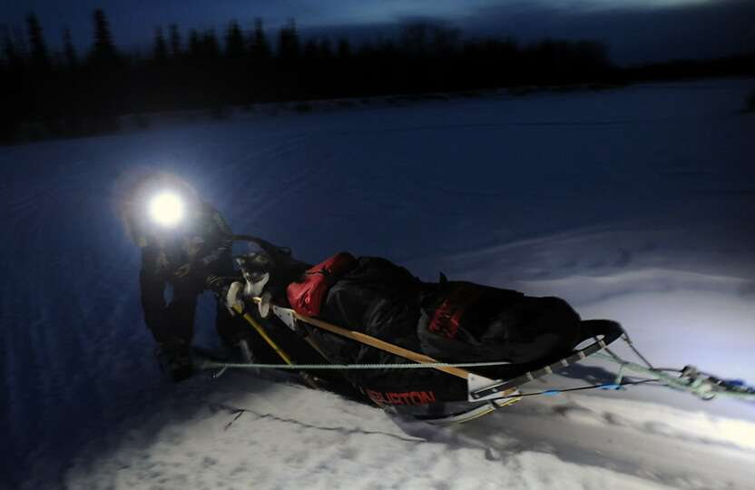 Iditarod musher Anna Berington arrives into the village of Nikolai, Alaska, with a dog named Skwentn