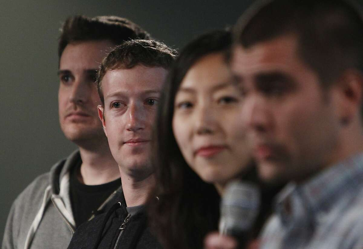 Mark Zuckerberg (second from left) stands with Chris Struhar (left), tech lead and Julie Zhuo (second from right), director of design as Chris Cox (right), vice president of product speaks during a press conference where a redesign of Facebook's News Feed was announced at it's headquarters on Thursday, March 7, 2013 in Menlo Park, Calif.