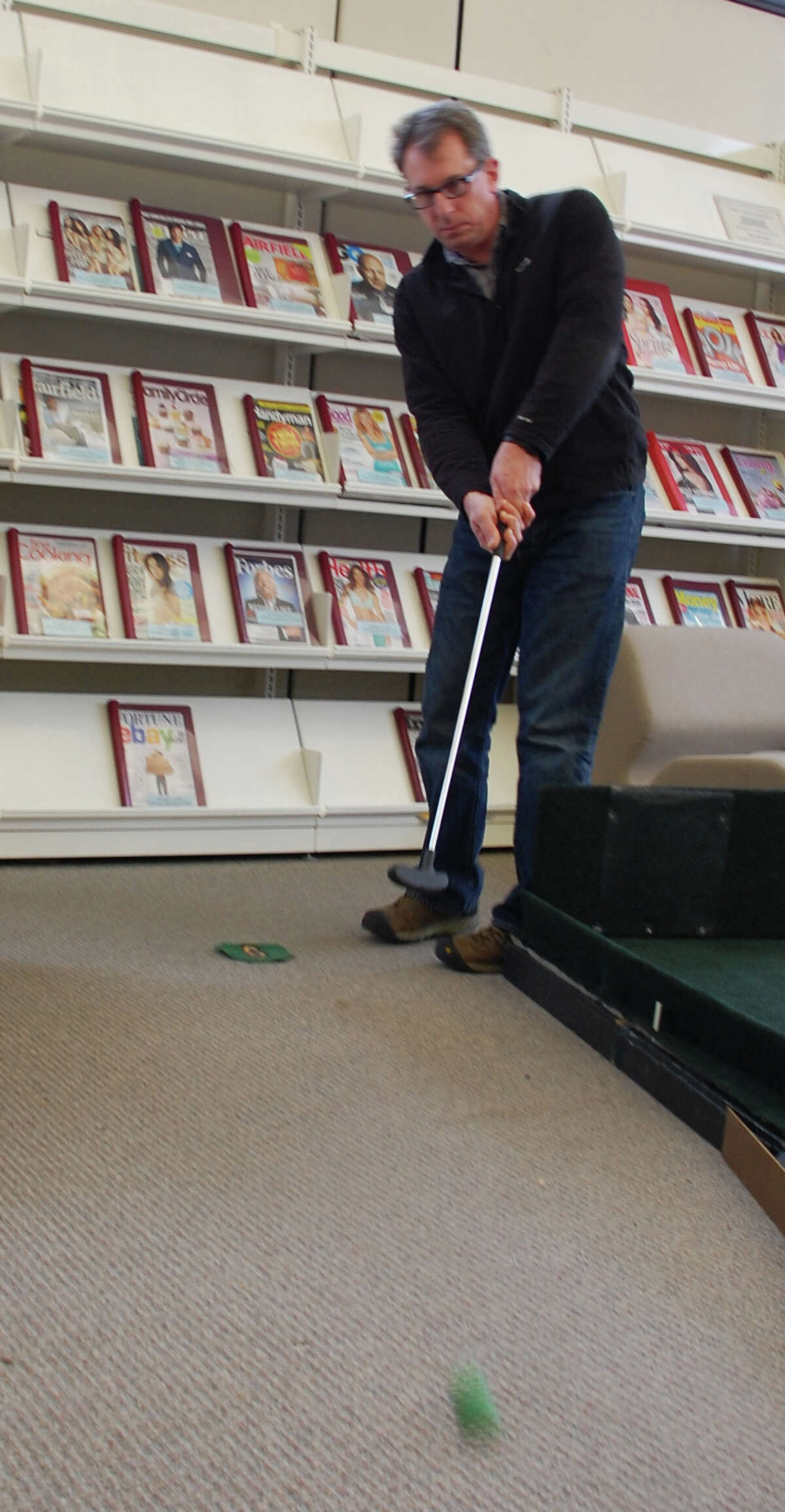 """Neal Fink of Fairfield unleashes a putt on a """"green"""" set up Sunday for a mini golf fundraiser at Fairfield Woods Branch Libray. FAIRFIELD CITIZEN, CT 3/3/13"""