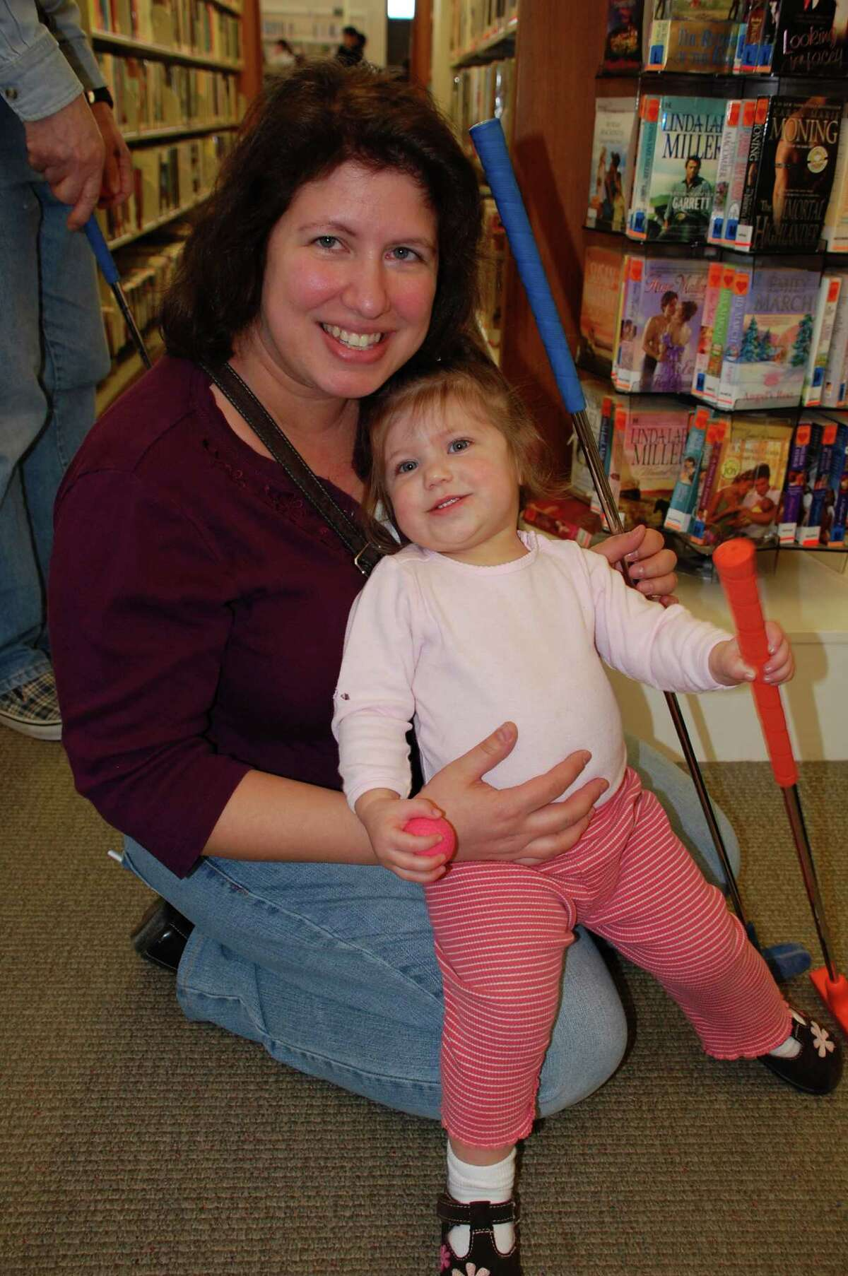 Gail Lacugna of Fairfield and her daughter, Lily, 17 months, enjoy a mini day of golf Sunday at the Fairfield Woods Branch Library. FAIRFIELD CITIZEN, CT 3/3/13