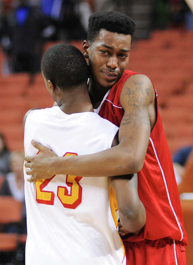Royal's Kenton Sams (11) gets a hug from Yates' Darrion Martin (23) after the UIL 3A semi final boys basketball game between Houston Yates and Royal high schools on Thurs., March 7, 2013 at the Frank Erwin Center in Austin, TX.  Final score Yates 81, Royal 70.