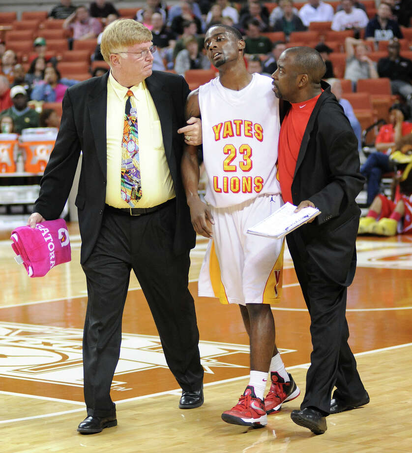 Yates' Darrion Martin (23) is escorted off the court with an injury during the UIL 3A semi final boys basketball game between Houston Yates and Royal high schools on Thurs., March 7, 2013 at the Frank Erwin Center in Austin, TX.