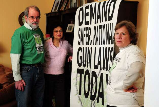 Lisa Labella, right, community outreach organizer for Connecticut Against Gun Violence (CAGV), and members Doug and Terry Sutherland, stand near one of the group's banners Thursday, Mar. 7, 2013 at Labella's home in Trumbull, Conn. Photo: Autumn Driscoll / Connecticut Post