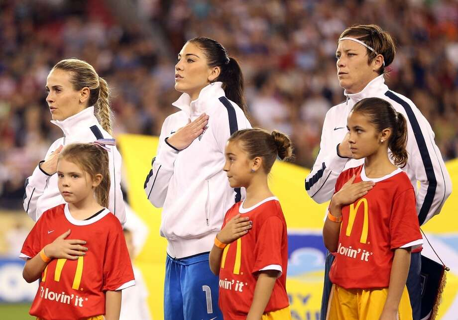 Goalkeeper Hope Solo, center, and Abby Wambach, right, of USA stand attended for the National Anthem before a game against Ireland at University of Phoenix Stadium on December 1, 2012, in Glendale, Arizona.   USA defeated Ireland 2-0.