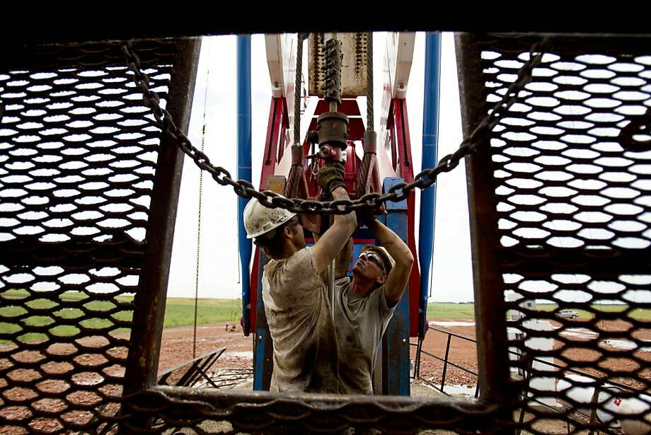 Austin Mitchell (left) and Ryan Lehto work on an oil derrick outside of Williston, N.D. There is an acute need at oil companies for skilled engineers to work at the newest complexes related to shale drilling. Photo: Gregory Bull, Associated Press