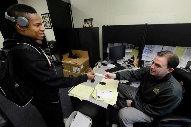 University at Albany mens' basketball coach Will Brown bought 400 tickets to this weekend's America East Tournament, and he is distributing them free to students from his campu office Thursday, March 7, 2013, in Albany, N.Y. Taariz Jones, left, of the mens' track and field team picks up his ticket to the game from coach Brown.  (Skip Dickstein/Times Union) Photo: SKIP DICKSTEIN / 10021475A