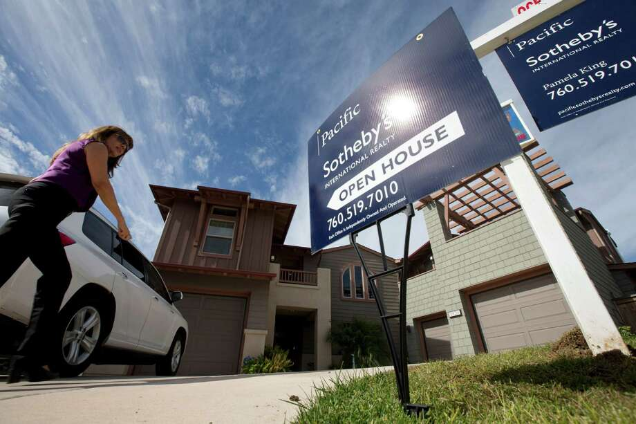 In this Wednesday, Nov. 14, 2012, photo, a woman walks towards a home for sale during a viewing for brokers in Leucadia, Calif. Mortgage buyer Freddie Mac said Thursday, Dec. 13, 2012, that the average rate on the 30-year loan dipped to 3.32 percent. That's below last week's rate of 3.34 percent. And it's just above the 3.31 percent, the lowest rate on records dating to 1971. (AP Photo/Gregory Bull, File) Photo: Gregory Bull / AP