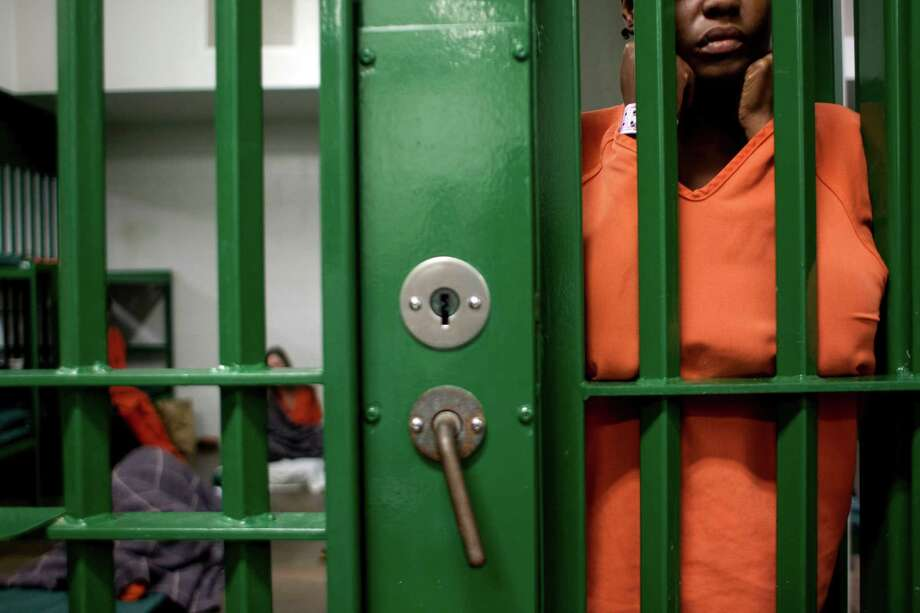 A female inmate locked up in an acute mental health cell block at the Harris County Sheriff's Office Mental Health Unit looks out of the cell. Michael Seal, M.D. executive director for health services, said 20 to 25 percent of the Harris County inmate population, or about 2100 people, are treated for mental illness. The inmates in the background felt more comfortable with their mats on the ground. Photo: Johnny Hanson, Houston Chronicle / © 2013  Houston Chronicle