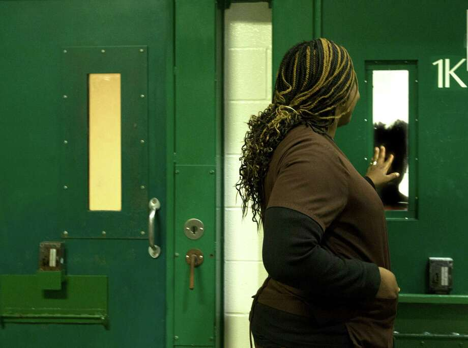 Oyeyemi Lawal, a psychological technician, talks to a female inmate who is locked up in an acute mental health cell block at the Harris County Sheriff's Office Mental Health Unit. Photo: Johnny Hanson, Houston Chronicle / © 2013  Houston Chronicle