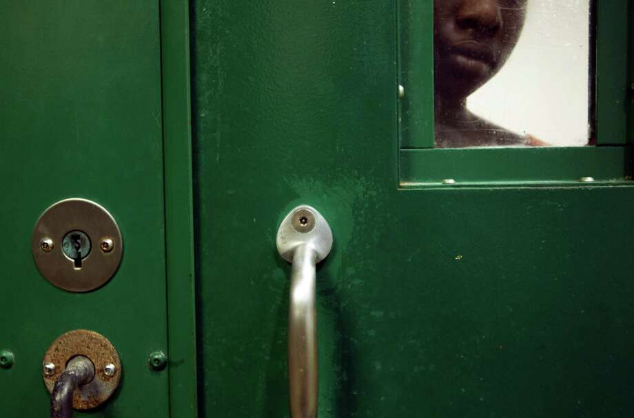 A female inmate is locked up in an acute mental health cell block at the Harris County Sheriff's Office Mental Health Unit. Photo: Johnny Hanson, Houston Chronicle / © 2013  Houston Chronicle