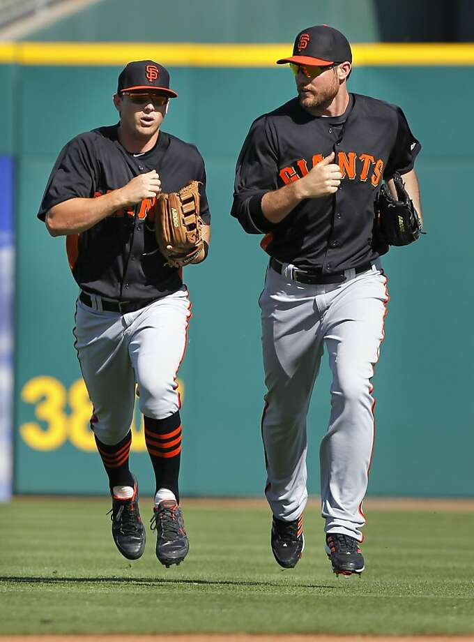 Giants' Gary Brown, (10,left) and Roger Kieschnick, (23) hustle back to the dugout after the sixth inning, as the San Francisco Giants went on to fall to the Cleveland Indians 6-4 at Goodyear Ballpark on Thursday Mar. 7, 2013, In Goodyear, Az. Photo: Michael Macor, The Chronicle