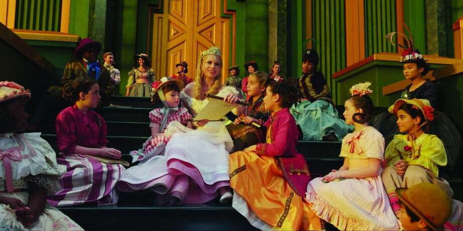 "Veronica Liu (far upper right, in tall-feathered  hat) and her brother Brandon Liu (far lower right, in brown hat), appear in this scene from ""Oz, the Great and Powerful."" (Walt Disney Pictures)"