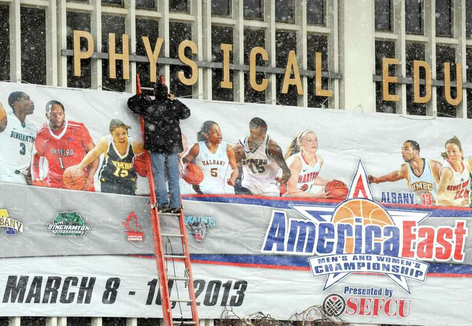 UAlbany assistant athletic director Mark Roczniak secures a banner for the America East basketball tournament on Thursday March 7, 2013 in Albany, N.Y. (Michael P. Farrell/Times Union) Photo: Michael P. Farrell