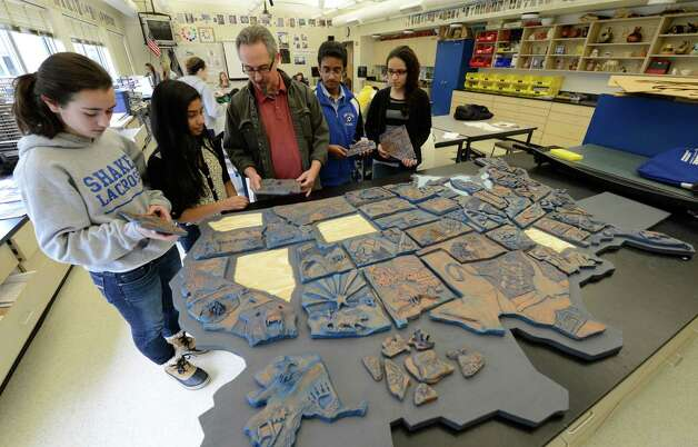 Artist Frank Giorgini, artist in residence with Shaker High School is joined by art students holding the the states that they designed Ryana Augstell, Wyoming, left Amulya Jakkani, Washington; Chathuranga Perera, Mississippi and Mariam Elasser, Nevada  March 7, 2013 in Latham, N.Y.  (Skip Dickstein/Times Union) Photo: SKIP DICKSTEIN / 10021455A