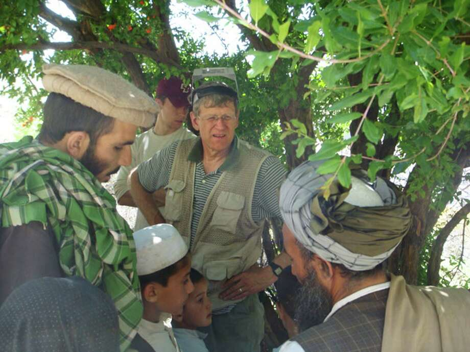 Tom Little, center, an optometrist from Delmar, working with the Noor eye clinic in Afghanistan.  Little was killed at age 61 in Afghanistan on Aug. 5, 2010 when he and 9 others were killed in an ambush.   (courtesy of Libby Little) Photo: Paul Buckowski