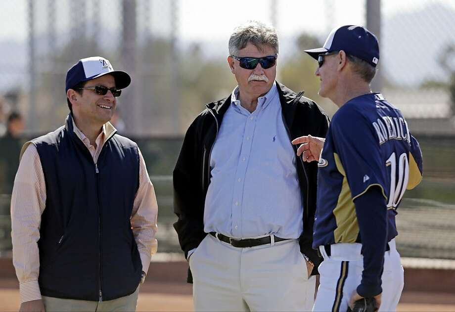 Milwaukee Brewers manager Ron Roenicke, right, talks to general manager Doug Melvin and owner Mark Attanasio during a spring training baseball workout Saturday, Feb. 16, 2013, in Phoenix. (AP Photo/Morry Gash) Photo: Morry Gash, Associated Press