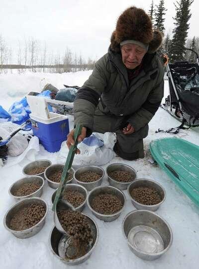Veteran Iditarod musher Rudy Demoski prepares food for his dog team at the McGrath, Alaska, checkpoi