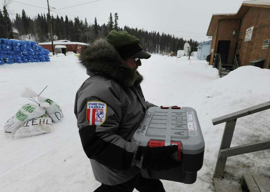 Iditarod veterinarian Mike Hicks of Cypress, Texas, carries supplies into the Anvik, Alaska, checkpoint as the Yukon River community prepares for the arrival of Iditarod mushers on Thursday, March 7, 2013. Photo: Bill Roth, McClatchy-Tribune News Service / Anchorage Daily News