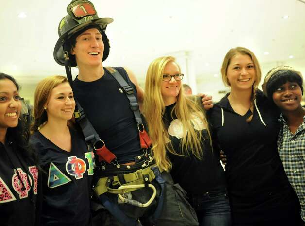 Albany firefighter Chip Cahill, center, poses with UAlbany Delta Phi Epsilon Sorority sisters before the annual Corning Tower Stair Climb on Thursday, March 7, 2013, in Albany, N.Y. The sorority members volunteer annually for the event, which benefits the Cystic Fibrosis Foundation. (Cindy Schultz / Times Union) Photo: Cindy Schultz / 10021215A