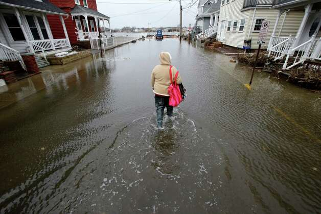 Carol Marelli walks down her flooded street Thursday, March 7, 2013, in Sea Bright, N.J., after an overnight storm. Flooding remained a problem in other shore towns. Water on roadways was also forcing closures in towns including Monmouth Beach, Absecon, Aberdeen, Egg Harbor Township and Wildwood. A coastal flood warning remains in effect until 9 a.m. Friday, but forecasters were not expecting Thursday's wind to be as strong as Wednesday, when gusts exceeding 60 mph were recorded in many places along the ocean. (AP Photo/Mel Evans) Photo: Mel Evans