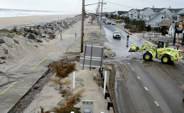 Crews clear a flooded road Thursday, March 7, 2013, in Sea Bright, N.J., after an overnight storm caused the ocean to breach a temporary dune. The lingering late-winter storm brought new damage Thursday to parts of the Jersey shore still struggling to recover from Superstorm Sandy. (AP Photo/Mel Evans) Photo: Mel Evans