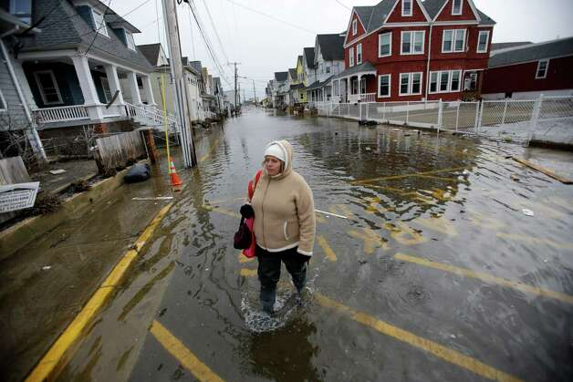 Carol Marelli walks down her flooded street Thursday, March 7, 2013, in Sea Bright, N.J., after an overnight storm. Flooding remained a problem in this and other shore towns. Water on roadways was also forcing closures in towns including Monmouth Beach, Absecon, Aberdeen, Egg Harbor Township and Wildwood. A coastal flood warning remains in effect until 9 a.m. Friday, but forecasters were not expecting Thursday's wind to be as strong as Wednesday, when gusts exceeding 60 mph were recorded in many places along the ocean. (AP Photo/Mel Evans) Photo: Mel Evans