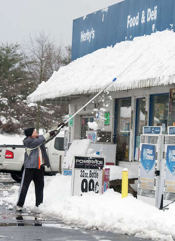 Nick Solanki, owner of Herby's Food and Deli clears off snow from an awning at his business Wednesday afternoon March 6, 2013 along Third Street in Harrisonburg, Va.. Some areas of the Central Shenandaoh Valley received over a foot of snow from Winter Storm Saturn.  (AP Photo/The Daily News-Record, Michael Reilly) Photo: Michael Reilly