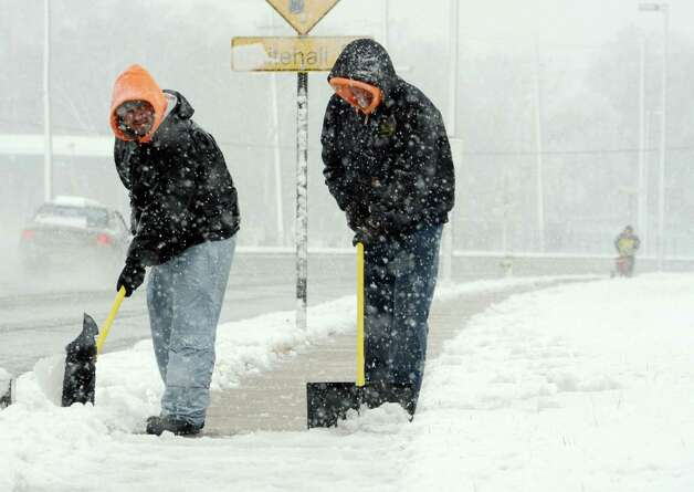 Nelson Duarte, left, and Wayne Edgar clear snow off sidewalks at Avington Park off Yellow Springs Rd. in Frederick, Md. early Wednesday morning Feb. 6, 2013.   (AP Photo/The Frederick News-Post,Sam Yu)