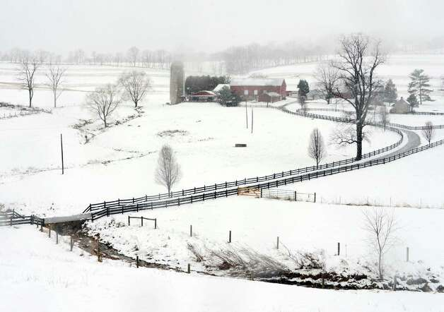 Falling snow and fog partially obscures the view of this farm off Harp Hill Rd. near Wolfsville, Md., during the winter storm Wednesday afternoon March 3, 2013.   Residents of far western Maryland are shaking off more than a foot of snow Wednesday.   (AP Photo/The Frederick News-Post,Sam Yu) Photo: Sam Yu