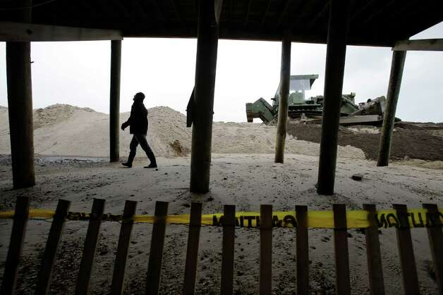 As heavy machinery is pushing sand to hastily rebuild a breached dune, Scott Clayton, of Bay Head, stops by his family's ocean front home damaged by Superstorm Sandy in Mantoloking, N.J., to check on new storm damage Thursday, March 7, 2013, after a storm overnight Thursday, with pounding surf broke through a temporary dune during the early-morning high tide. Flooding also remained a problem in other shore towns.Water on roadways was also forcing closures in towns including Monmouth Beach, Absecon, Aberdeen, Egg Harbor Township and Wildwood. (AP Photo/Mel Evans) Photo: Mel Evans