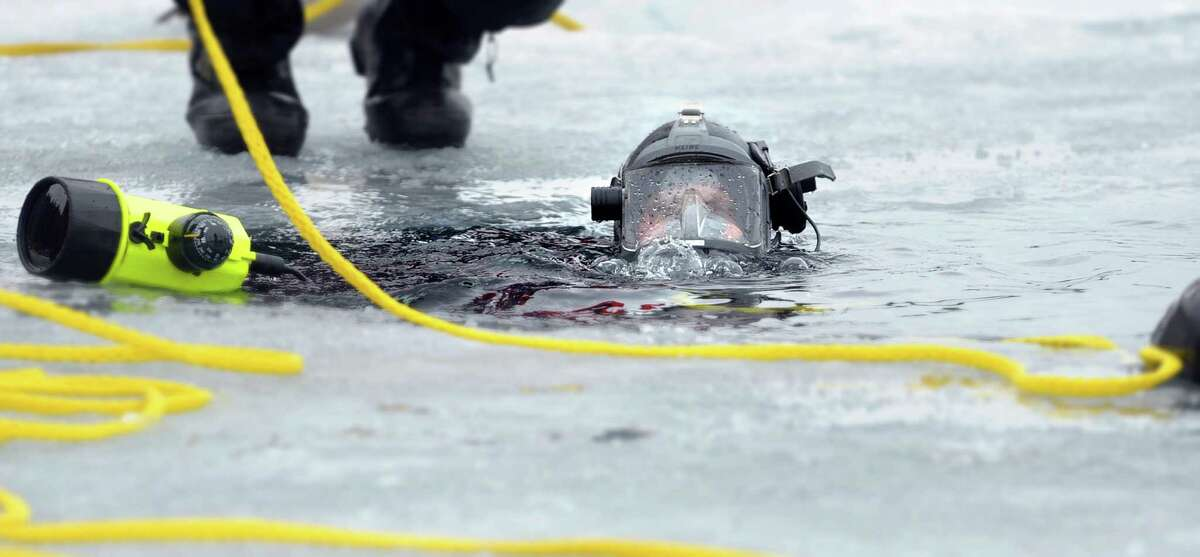 New York State Trooper Jon Gardner with Troop E out of the Rochester area starts to go under water as New York State Police and Delaware State Police divers went through training exercises on Lake George on Thursday, March 7, 2013 in Lake George, NY. (Paul Buckowski / Times Union)