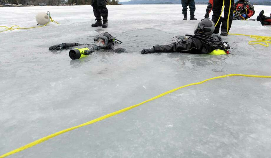 New York State Troopers Jon Gardner, left, and Ken Kline, right, with Troop E out of the Rochester area, rest on the edge of the ice after running through training exercises on Lake George on Thursday, March 7, 2013 in Lake George, NY.    (Paul Buckowski / Times Union) Photo: Paul Buckowski