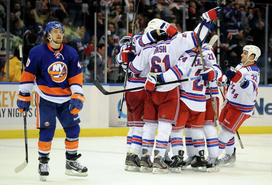 New York Islanders' Michael Grabner (40) skates off the ice as the New York Rangers celebrate the goal by Marian Gaborik that won the NHL hockey game 2-1 in overtime on Thursday, March 7, 2013, at Nassau Coliseum  in Uniondale, N.Y. Grabner scored the Islanders' only goal. (AP Photo/Kathy Kmonicek) Photo: Kathy Kmonicek