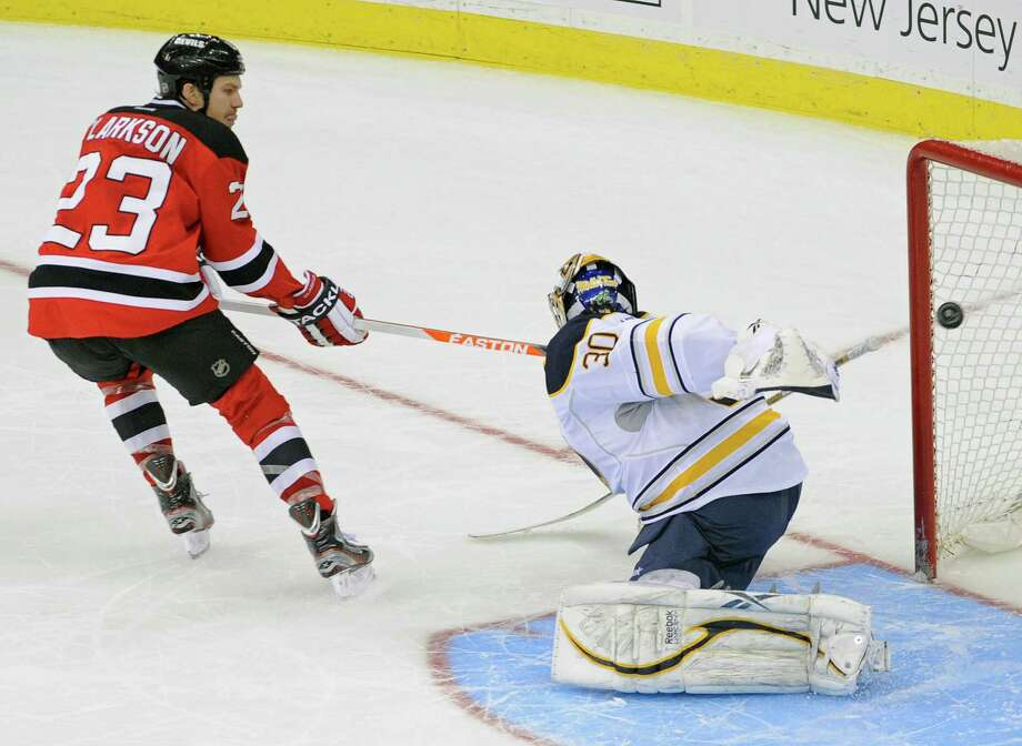New Jersey Devils' David Clarkson scores against Buffalo Sabres goaltender Ryan Miller, right, during the shootout in an NHL hockey game Thursday, March 7, 2013, in Newark, N.J. The Devils won 3-2. (AP Photo/Bill Kostroun) Photo: Bill Kostroun