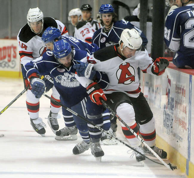 Phil DeSimone of the Albany Devils, right,  battles for the puck with Danick Gauthier of Syracuse du