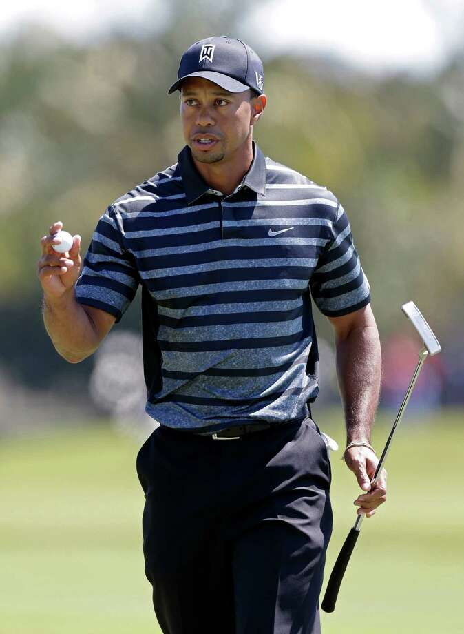 Tiger Woods acknowledges the fans after  par on the 10th hole during the first round play at the Cadillac Golf Championship, in Doral, Fla., Thursday March 7, 2013. (AP Photo/Wilfredo Lee) Photo: Wilfredo Lee
