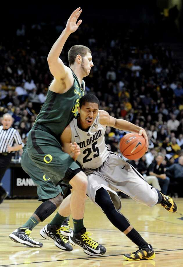 Colorado's Spencer Dinwiddie (25) drives on Oregon's Ben Carter during the first half of their NCAA college basketball game, Thursday, March 7, 2013, in Boulder, Colo. (AP Photo/The Daily Camera, Cliff Grassmick) NO SALES; MAGS OUT; TV OUT Photo: Cliff Grassmick
