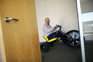 Ask.com CEO Doug Leeds rides a 3 wheel trike through the halls of his company's offices in downtown Oakland, CA Wednesday February 20th, 2013.